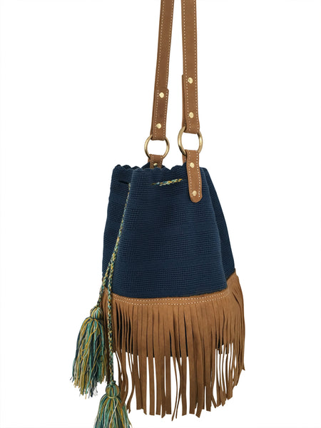 Side angle image of Wayuu bucket bag purse with brown leather strap and fringe; bag is solid navy with colored tassels and drawstring