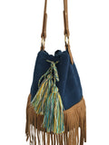 Close up image of Wayuu bucket bag purse with brown leather strap and fringe; bag is solid navy with colored tassels and drawstring