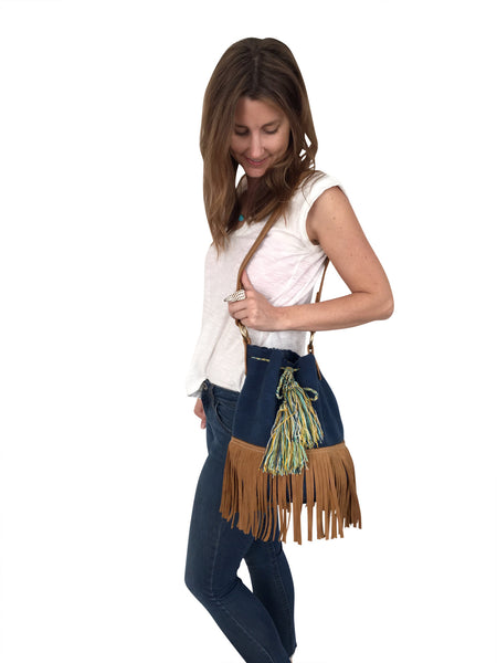 On body image of Wayuu bucket bag purse with brown leather strap and fringe; bag is solid navy with colored tassels and drawstring