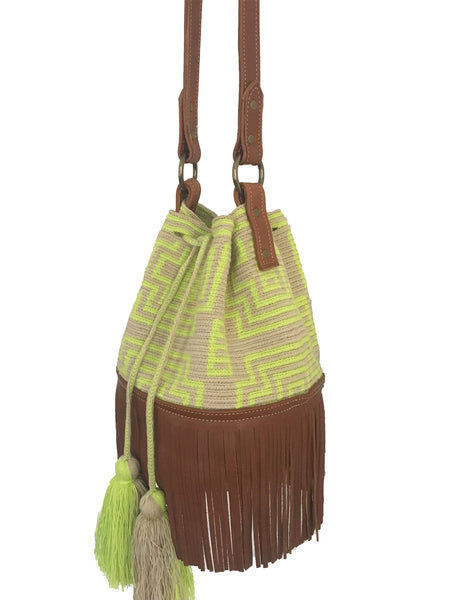 Side angle image of Wayuu bucket bag purse with brown leather strap and fringe; bag is light tan with neon yellow design