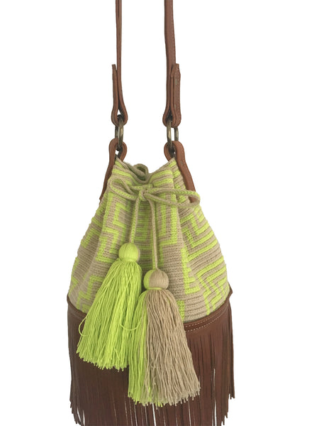 Close up image of Wayuu bucket bag purse with brown leather strap and fringe; bag is light tan with neon yellow design