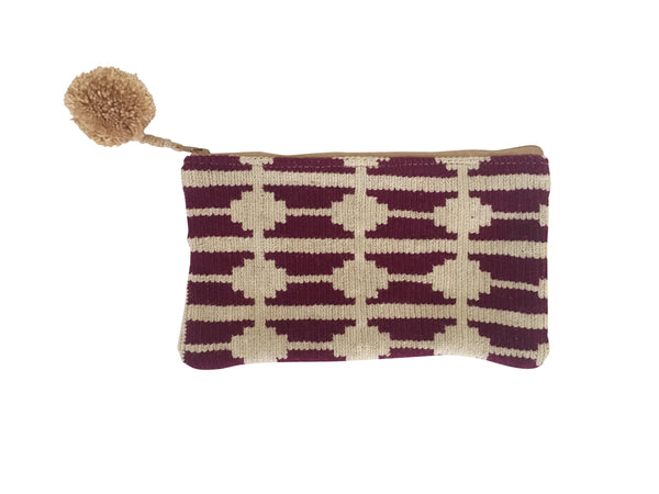 Image of handmade Wayuu zipper pouch with woven textile in burgundy and light tan design; pouch has colorful pompom and a zipper at the top