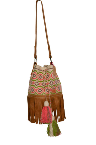 Image of Wayuu bucket bag purse with caramel brown leather strap, fringe with drawstring and tassels; bag is tan with light brown, light pink and light green circular design
