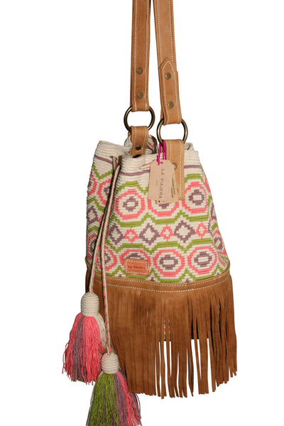 Side angle image of Wayuu bucket bag purse with caramel brown leather strap, fringe with drawstring and tassels; bag is tan with light brown, light pink and light green circular design