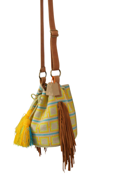 Side angle image of one strand Wayuu bucket bag purse with brown leather strap and fringe and tassels; bag is light tan with bright yellow and orange squares and blue lines