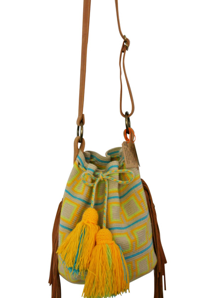 Close up image of one strand Wayuu bucket bag purse with brown leather strap and fringe and tassels; bag is light tan with bright yellow and orange squares and blue lines