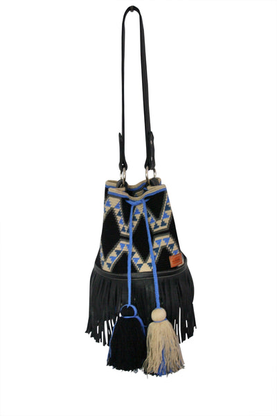 Image of Wayuu bucket bag purse with black leather strap and fringe and tassels; bag black with geo designs in light tan and blue colors