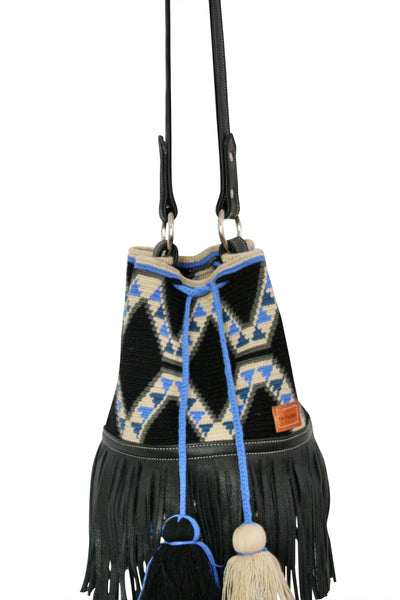 Close up image of Wayuu bucket bag purse with black leather strap and fringe and tassels; bag black with geo designs in light tan and blue colors