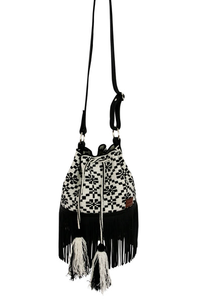 Image of Wayuu bucket bag purse with black leather strap and fringe and tassels; bag is white with black flower detail