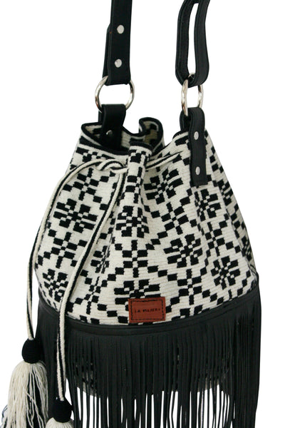 Side angle image of Wayuu bucket bag purse with black leather strap and fringe and tassels; bag is white with black flower detail
