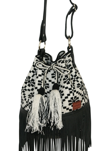 Close up image of Wayuu bucket bag purse with black leather strap and fringe and tassels; bag is white with black flower detail
