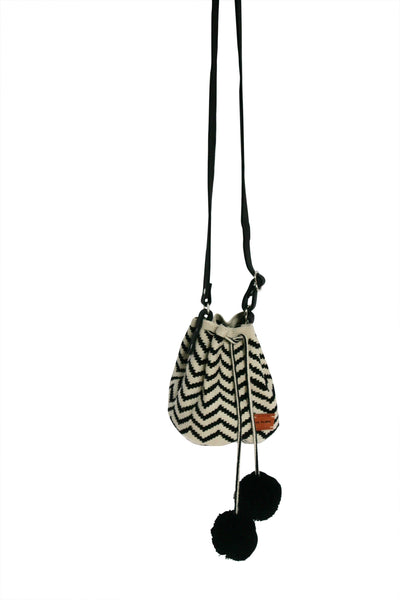 Image of Wayuu mini mochila bucket bag purse with adjustable leather strap, drawstring and two pompoms; bag has zigzag design colored black and off white