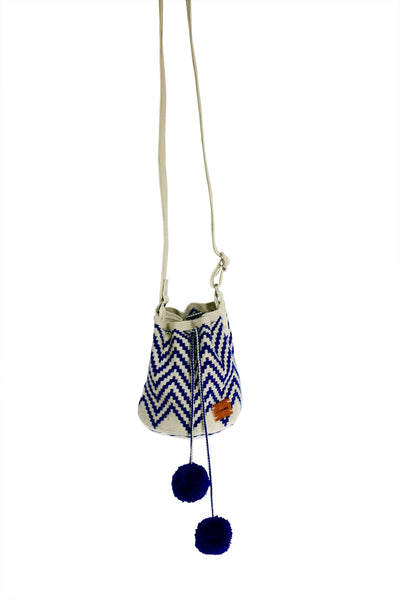 Image of Wayuu mini mochila bucket bag purse with adjustable leather strap, drawstring and two pompoms; bag has off white base with blue zig zag pattern