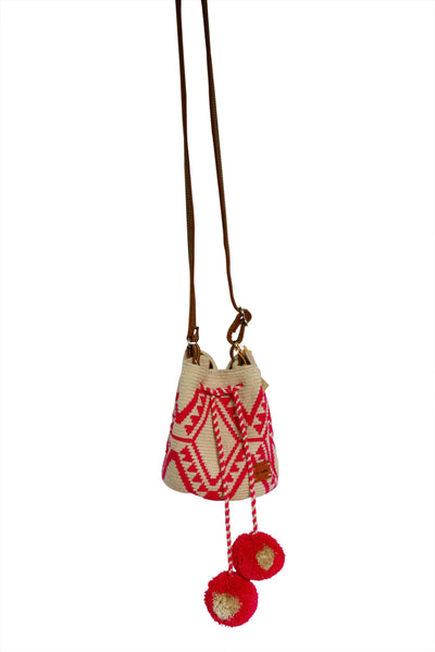 Image of Wayuu mini mochila bucket bag purse with adjustable leather strap, drawstring and two pompoms; bag has light tan base with bright pink design