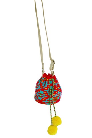 Image of Wayuu mini mochila bucket bag purse with adjustable leather strap, drawstring and two pompoms; bag has bright pink base with multi color design