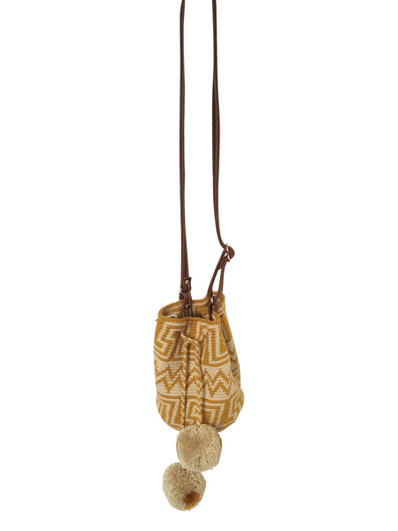 Image of Wayuu mini mochila bucket bag purse with adjustable leather strap, drawstring and two pompoms; bag has geo patterns with gold color on light tan base