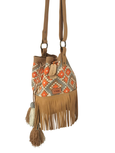 Side angle image of Wayuu bucket bag purse with brown adjustable leather strap and fringe and tassels; bag is tan with orange, white and blue design