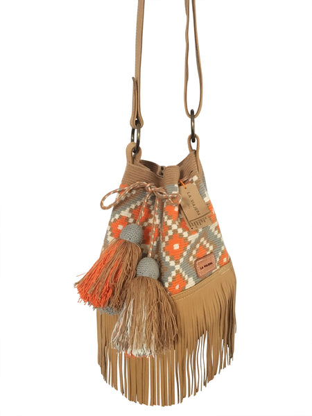 Close up Image of Wayuu bucket bag purse with brown adjustable leather strap and fringe and tassels; bag is tan with orange, white and blue design
