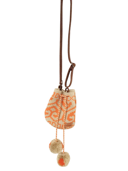 Image of Wayuu mini mochila bucket bag purse with adjustable leather strap, drawstring and two pompoms; bag has geo patterns in orange on light tan base bag