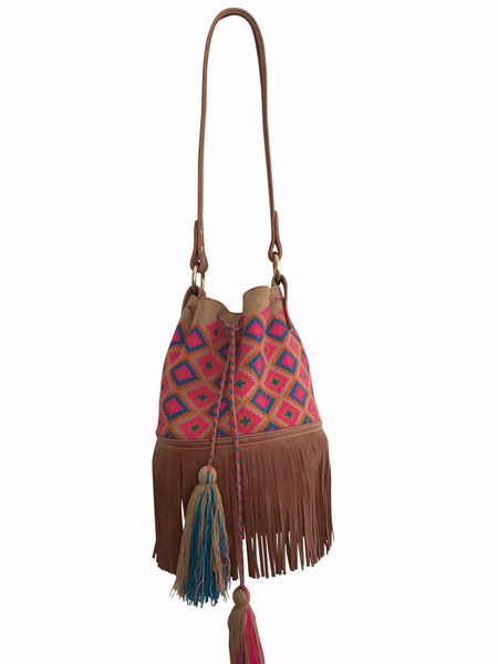 Image of Wayuu mochila purse with brown leather strap and fringe; bag is tan with magenta orange blue detail
