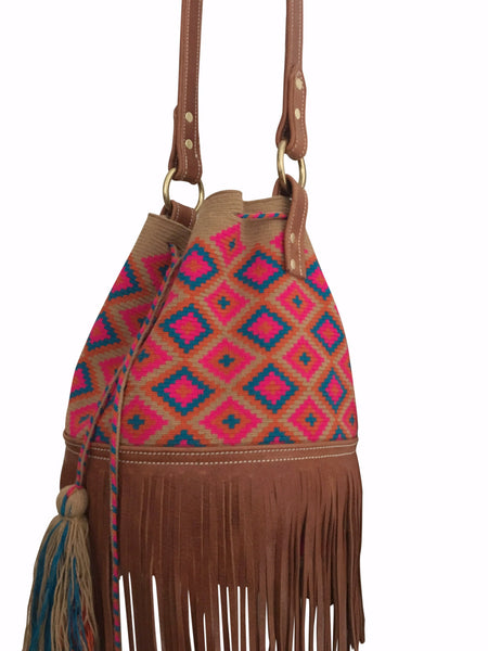 Side angle image of Wayuu mochila purse with brown leather strap and fringe; bag is tan with magenta orange blue detail