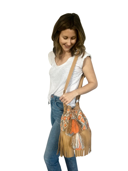 On body image of Wayuu bucket bag purse with brown adjustable leather strap and fringe and tassels; bag is tan with orange, white and blue design