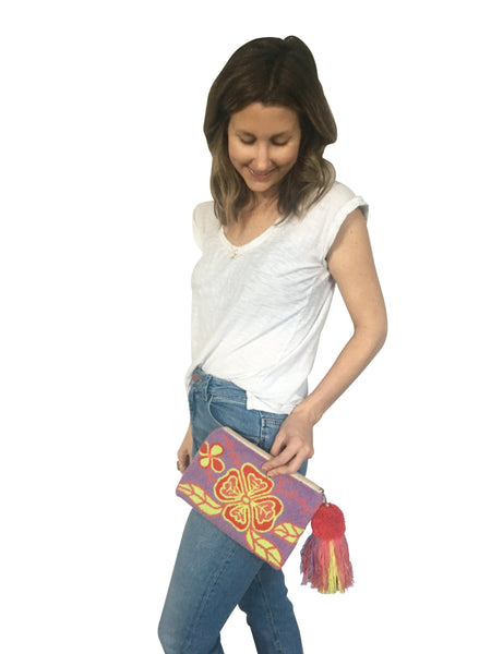 On body iImage of Wayuu tapizado small clutch purse with pom pom tassel; rectangular shape colored light purple, red, pink, bright yellow