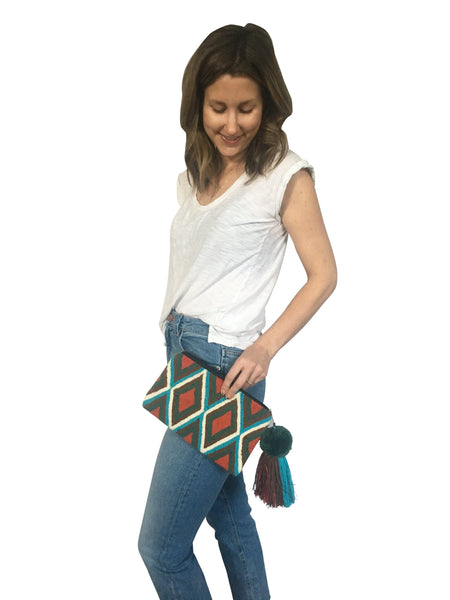 On body image of Wayuu tapizado small clutch purse with pom pom tassel; rectangular shape colored teal, turquoise, brown, white and orange