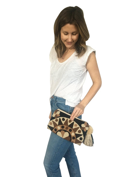 On body image of Wayuu tapizado small clutch purse with pompom tassel; rectangular shape colored a mix of neutral browns