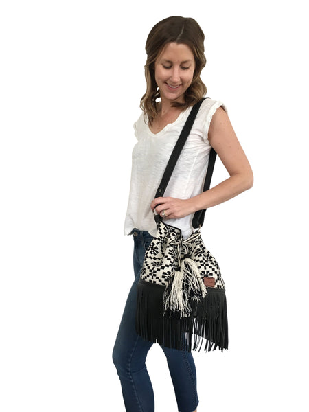 On body image of Wayuu bucket bag purse with black leather strap and fringe and tassels; bag is white with black flower detail