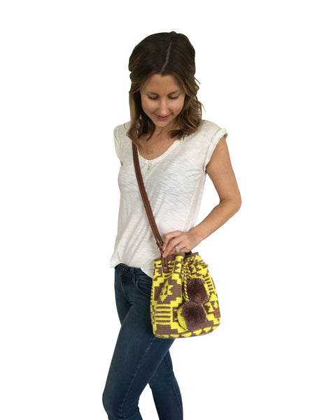 On body image of Wayuu mini mochila bucket bag purse with adjustable leather strap, drawstring and two pompoms; bag has brown base with bright yellow design