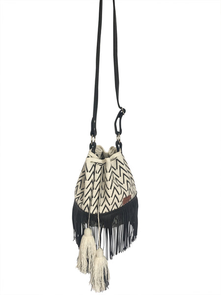 Image of Wayuu bucket bag purse with black leather strap and fringe and tassels; bag is white with black detail