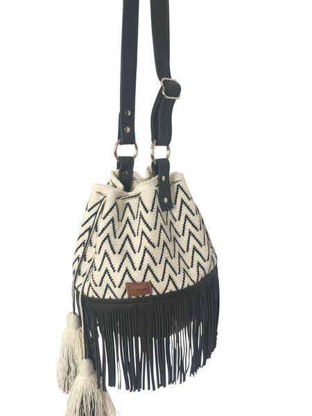 Side angle image of Wayuu bucket bag purse with black leather strap and fringe and tassels; bag is white with black detail
