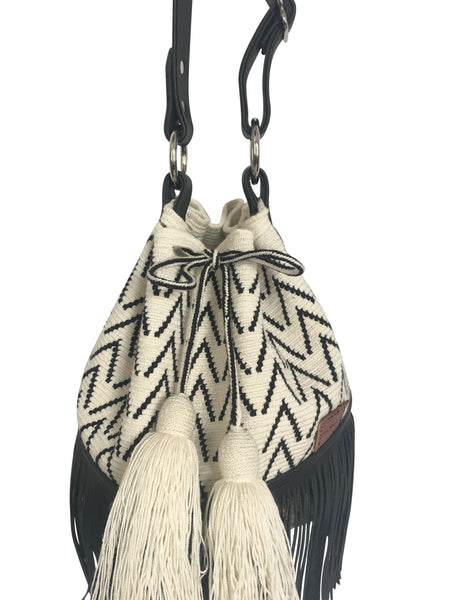 Close up angle image of Wayuu bucket bag purse with black leather strap and fringe and tassels; bag is white with black detail