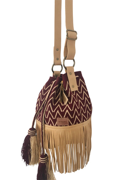 Side angle image of Wayuu bucket bag purse with brown leather strap and fringe and tassels; bag is burgundy with light tan detail