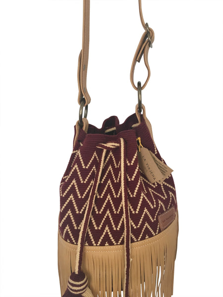 Close up image of Wayuu bucket bag purse with brown leather strap and fringe and tassels; bag is burgundy with light tan detail
