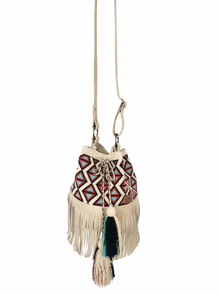 Image of Wayuu bucket bag purse with oatmeal colored leather strap and fringe with tassels; bag is light base with black, blue and red detail