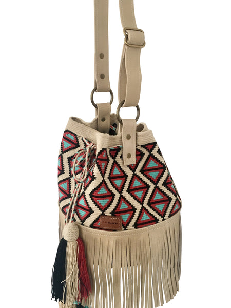 Side angle image of Wayuu bucket bag purse with oatmeal colored leather strap and fringe with tassels; bag is light base with black, blue and red detail