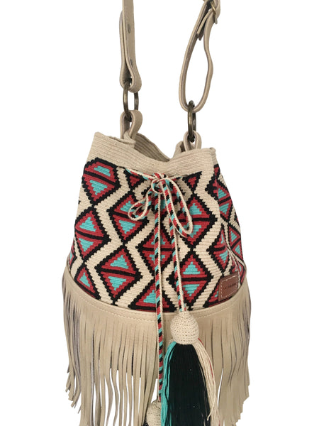 Close up image of Wayuu bucket bag purse with oatmeal colored leather strap and fringe with tassels; bag is light base with black, blue and red detail
