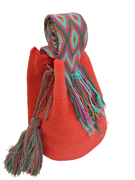 Side angle image of two strand Wayuu mochila bag, drawstring crossbody bag with tassels - base color coral with colorful strap