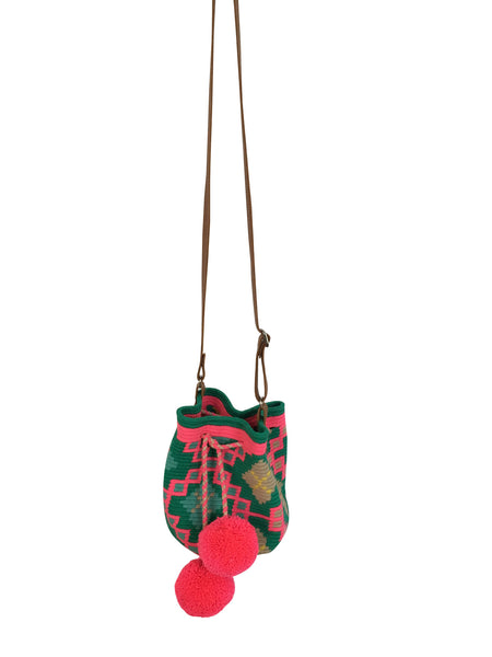 Image of Wayuu mini mochila bucket bag purse with adjustable leather strap, drawstring and two pompoms; bag is teal base with bright pink, blue, tan, yellow design