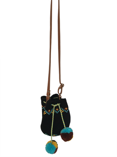 Image of Wayuu mini mochila bucket bag purse with adjustable leather strap, drawstring and two pompoms; bag is black base with some yellow, brown, blue design
