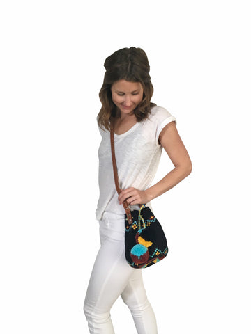 On body image of Wayuu mini mochila bucket bag purse with adjustable leather strap, drawstring and two pompoms; bag is black base with some yellow, brown, blue design