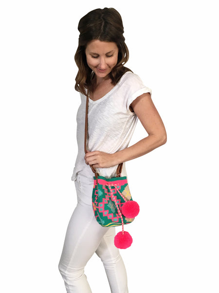 On body image of Wayuu mini mochila bucket bag purse with adjustable leather strap, drawstring and two pompoms; bag is teal base with bright pink, blue, tan, yellow design