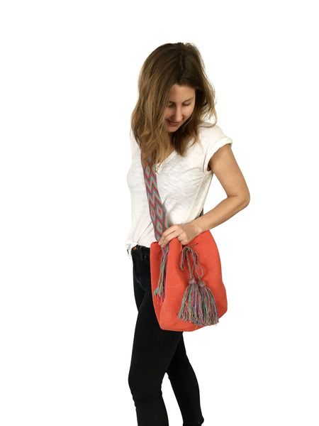 On body image of two strand Wayuu mochila bag, drawstring crossbody bag with tassels - base color coral with colorful strap