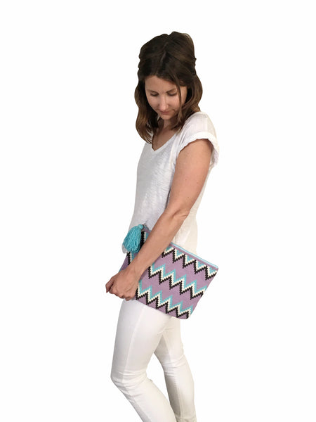 On body image of Wayuu tejido large clutch purse with tassel; rectangular shape colored light purple base with light blue, white, dark grey, zig zags across bag