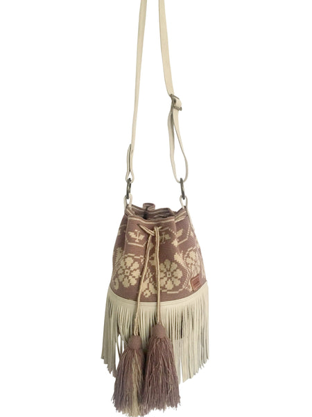Image of Wayuu bucket bag purse with oatmeal color leather strap and fringe and tassels; bag is light purple with cream flower desing