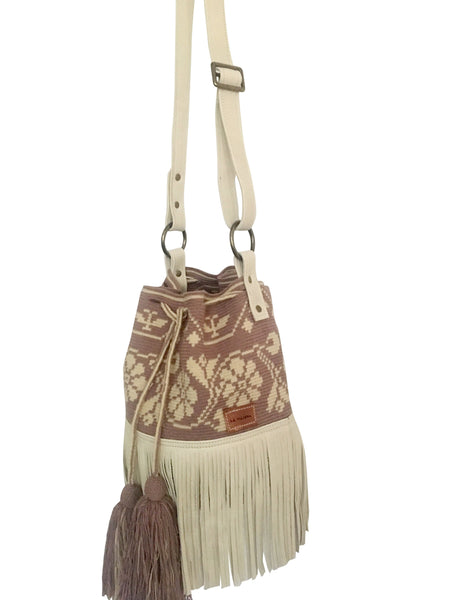 Side image of Wayuu bucket bag purse with oatmeal color leather strap and fringe and tassels; bag is light purple with cream flower desing