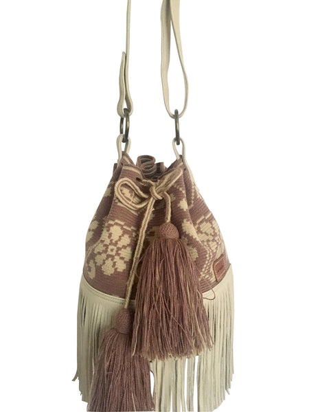 Close up image of Wayuu bucket bag purse with oatmeal color leather strap and fringe and tassels; bag is light purple with cream flower desing
