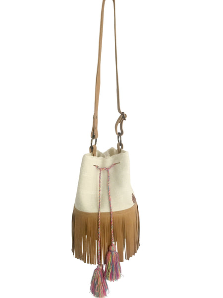 Image of Wayuu bucket bag purse with brown color leather strap and fringe and tassels; bag is white with colorful tassels